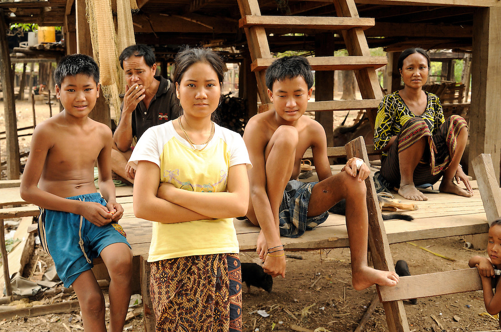 """Sompong, age 15 (center right), shows the wounds to his arm and leg when he and his brother tried to open a Russian 37mm anti-aircraft shell.  His cousin Soy Kiengphaserth, age 21 (center left), works in the Mines Advisory Group (MAG) female team.  She and the team found him on their way home from work and rushed him to the hospital while he was treated by a MAG Medic on the way.  Sompong's mother, Mone (far right), said, """"If not for MAG they might not have survived.""""..Many accidents occur in Laos when people try to open live weapons to sell the explosives and scrap metal. ..Laos was part of a """"Secret War"""", waged within its borders primarily by the USA and North Vietnam.  Many left over weapons supplied by China and Russia continue to kill.  However, between 90 and 270 million fist size cluster bombs were dropped on Laos by the USA, with a failure rate up to 30%.  Millions of live cluster bombs still contaminate large areas of Laos causing death and injury.  The US Military dropped approximately 2 million tons of bombs on Laos making it, per capita, the most heavily bombed country in the world. ..The women of Mines Advisory Group (MAG) work everyday under dangerous conditions removing unexploded ordinance (UXO) from fields and villages...***All photographs of MAG's work must include (either on the photo or right next to it) the credit as follows:  Mine clearance by MAG (Reg. charity)***."""