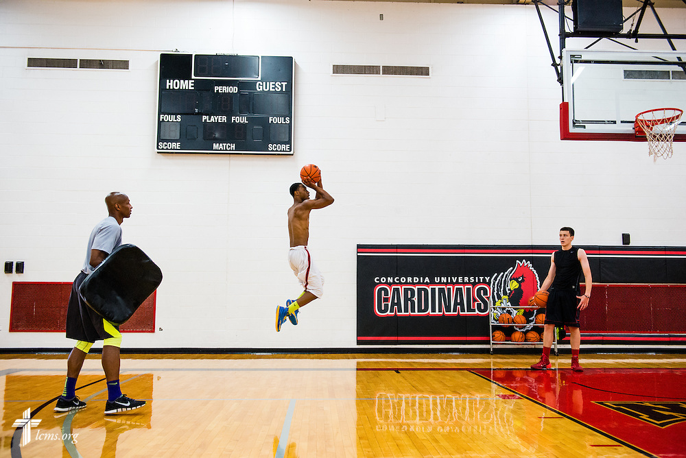 Marvin Fox (left), player development coach in the Concordia Mens' basketball team, watches as James McPherson heads to the basket during practice at Concordia University Ann Arbor on Thursday, July 3, 2014, in Ann Arbor, Mich. Student Trevor Travis (right) watches McPherson. LCMS Communications/Erik M. Lunsford