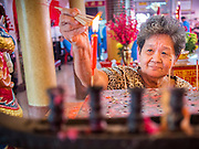 "09 FEBRUARY 2014 - HAT YAI, SONGKHLA, THAILAND:  A woman lights candles in the Chao Mae Tubtim Shrine (Ruby Goddess Shrine) on 108 Hainanese Ancestors Memorial Day in Hat Yai, Songkhla, Thailand. Hainanese communities around the world celebrate ""108 Hainanese Ancestors Memorial Day."" The day honors the time when 109 Hainanese villagers fleeing life in Hainan (an island off of the southwest coast of China, near Vietnam) washed up in what is now Vietnam and were killed by Vietnamese authorities because authorities thought they were pirates. The Vietnamese built a temple on the site and named it ""Zhao Yin Ying Lie."" Many Vietnamese fisherman credit prayers at the temple to saving their lives during violent storms and now ""108 Hainanese Ancestors Memorial Day"" is celebrated in Hainanese communities around the world. Hat Yai, the economic center of southern Thailand has a large Hainanese population.   PHOTO BY JACK KURTZ"