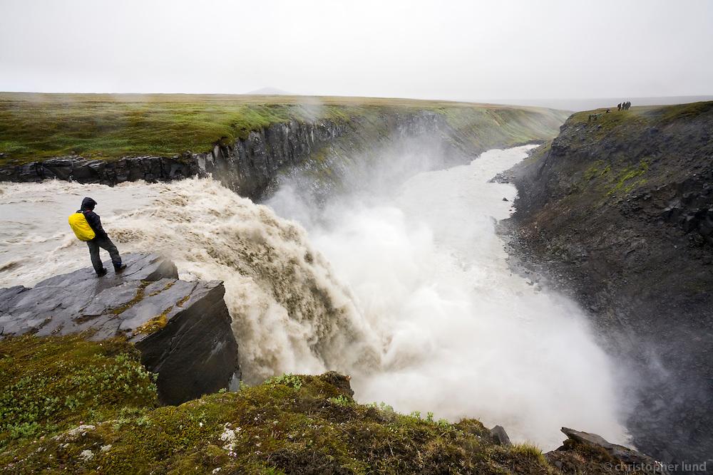 Hiker by T&ouml;frafoss (Magical waterfall) waterfall in river Kringils&aacute; in &Ouml;r&aelig;fi, Highlands of Iceland. Kringils&aacute; is a glacier river that will largely disappear due to the H&aacute;lsl&oacute;n resovoir that is being made for K&aacute;rahnj&uacute;kar Power Plant.<br /> <br /> T&ouml;frafoss &iacute; Kringils&aacute;. G&ouml;nguh&oacute;pur &aacute; vegum Augnabliks vir&eth;ir fyrir s&eacute;r &oacute;tr&uacute;legan kraftinn &iacute; fossinum.