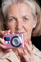 Portrait of senior woman holding camera against black background