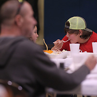 Caleb Roberson, 14, sits by himself as enjoys his first few bites of his Thanksgiving lunch at Tupelo's Salvation Army Thursday afternoon.