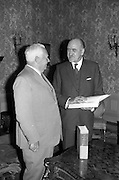"""08/05/1964<br /> 05/08/1964<br /> 08 May 1964<br /> Presentation of a """"Digest of International Law"""".  Mr. Frank Aiken T.D., Minister for External Affairs examines on of the volumes presented to him by Mr. Matthew McCloskey (left), U.S. Ambassador at Iveagh House, Dublin. The Digest was the first produced since the Second World War, prepared by Assistant Legal Advisor Majorie Whiteman and published by the U.S. Department of State. DFA,"""