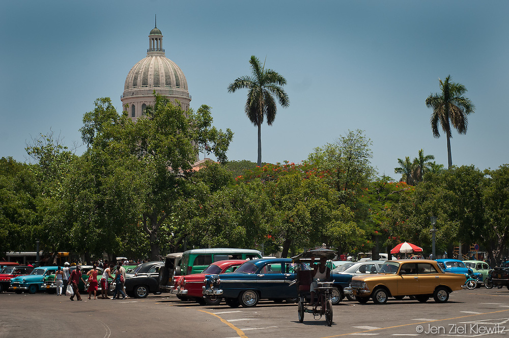 Vintage car taxis, or maquinas, and bicitaxis gather at a central departure point next the Parque de la Fraternidad, south of the Capitolio building in Havana, Cuba. Photo by Jen Klewitz