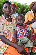 Scovia with baby Ronald (1 year old)  Women from Kitahurira, the only Batwa tribe settlement in Mpungu district, wait with their children to attend the Bwindi Community Hospital outreach clinic. The mothers and children receive nutrition information and vaccinations from the hospital nurse.  Bwindi Community Hospital provides different outreach clinics everyday for the surrounding area around Buhoma. The Mpungu district is on the edge of the Bwindi Impenetrable Forest, Western Uganda.