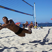 A local dives for the ball while playing foot volley, a hybrid game combining beach volley ball and football at Copacabana beach, Rio de Janeiro,  Brazil. 4th July 2010. Photo Tim Clayton..The beaches of Rio de Janeiro, provide the ultimate playground for locals and tourists alike. Beach activity is in abundance as beach volley ball, football and a hybrid of the two, foot volley, are played day and night along the length and breadth of Rio's beaches. .Volleyball nets and football posts stretch along the cities coastline and are a hive of activity particularly at it's most famous beaches Copacabana and Ipanema. .The warm waters of the Atlantic Ocean provide the ideal conditions for a variety of water sports. Walkways along the edge of the beaches along with exercise stations and cycleways encourage sporting activity, even an outdoor gym is available at the Parque Do Arpoador overlooking the ocean. .On Sunday's the main roads along the beaches of Copacabana, Leblon and Ipanema are closed to traffic bringing out thousands of people of all ages to walk, run, jog, ride, skateboard and cycle more than 10 km of beachside roadway. .This sports mad city is about to become a worldwide sporting focus as they play host to the world's biggest sporting events with Brazil hosting the next Fifa World Cup in 2014 and Rio de Janeiro hosting the Olympic Games in 2016...