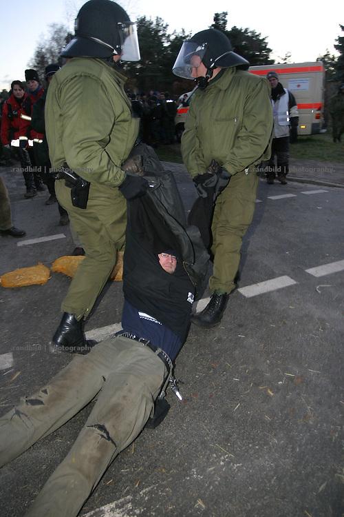 Polizisten schleifen einen Atomkraftgegner von der Strasse in Gorleben als sie eine Sitzblockde gegen einen Castortransport räumen...Police clear up a road blocked by anti nuclear activists in Gorleben.