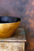 Weathered decorative gold bowl on an old metal box.