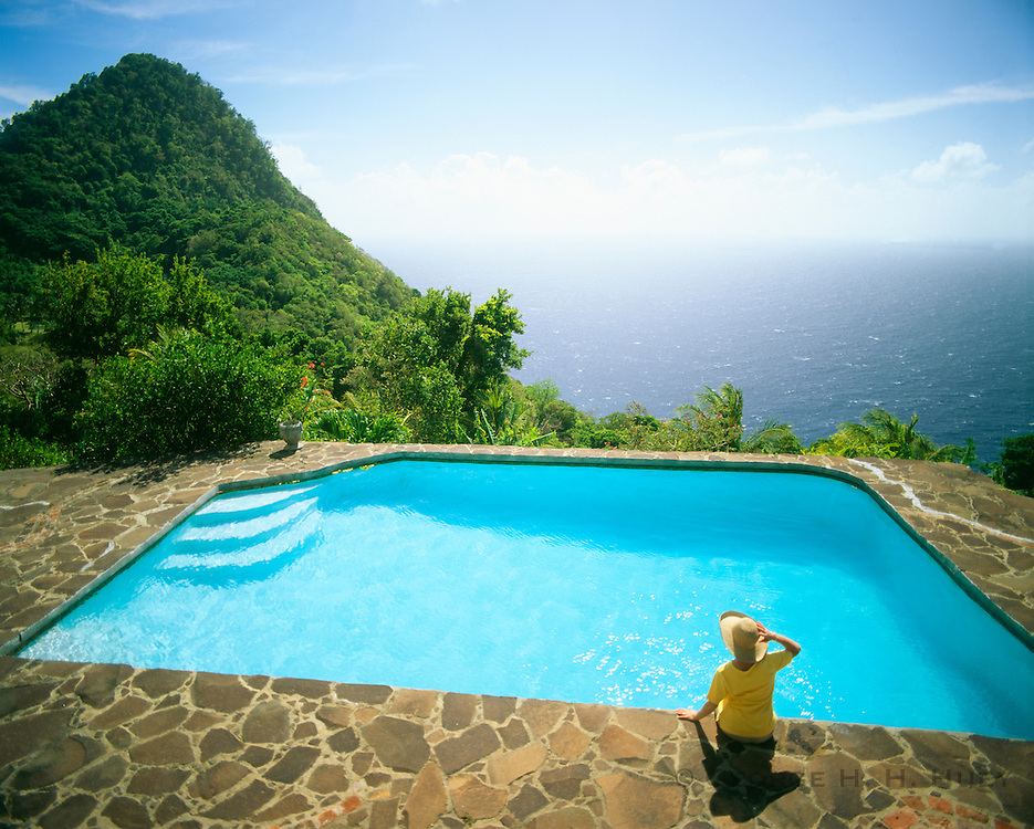 6203-1062B ~ Copyright: George H. H. Huey ~ Tourist at pool at Petite Coulibri, 1000 feet above the ocean, with the Martinique Channel in distance. Dominica. Windward Islands, Lesser Antilles. Caribbean.