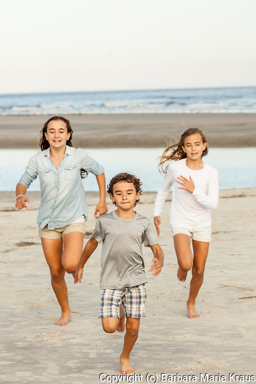 Two sisters and their brother race each other on the beach.