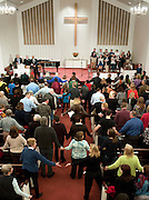 "Parishioners reach for each other's hands as they sing the song ""We Shall Overcome"" at the end of an interfaith service at Newtown Congregational Church in Newtown, Conn., Sunday, Jan. 20, 2013. (AP Photo/Jessica Hill)"