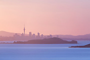 As the sun dips below the horizon, the sky cools to a gentle pink sunset over Auckland city, New Zealand
