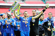 AFC Wimbledon defender Jon Meades (12) and AFC Wimbledon goalkeeper Kelle Roos (29) celebrate promotion with the trophy in front of the AFC Wimbledon fans after the Sky Bet League 2 play off final match between AFC Wimbledon and Plymouth Argyle at Wembley Stadium, London, England on 30 May 2016. Photo by Graham Hunt.