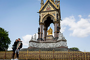 A couple hug in front of the golden ironwork at the Albert Memorial in Kensington Park, on 20th August 2019, in London, England. The Albert Memorial, directly north of the Royal Albert Hall in Kensington Gardens, London, was commissioned by Queen Victoria in memory of her beloved husband Prince Albert, who died in 1861. Designed by Sir George Gilbert Scott in the Gothic Revival style, it takes the form of an ornate canopy or pavilion 176 feet tall, in the style of a Gothic ciborium over the high altar of a church, sheltering a statue of the prince facing south. It took over ten years to complete, the £120,000 cost met by public subscription.
