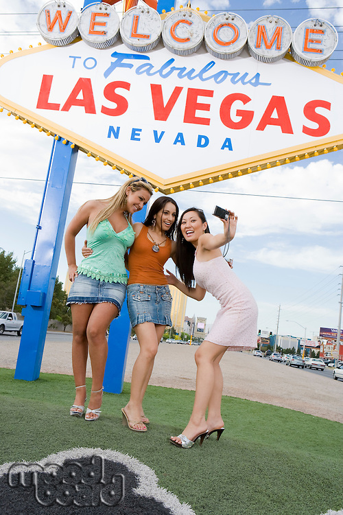 Three women taking picture in front of Las Vegas welcome sign, Nevada, USA