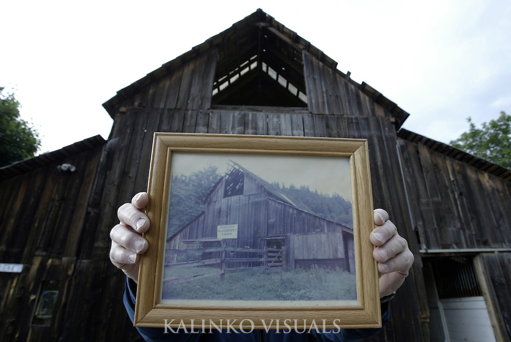 06132007-  Canter-Berry Farms..Doug Cross (CQ) owner of Canter-Berry Farms off Green Valley Road in Auburn holds up a photograph of his barn from 1979. The barn, built in 1879, is now used as a place for Doug and his wife Clarissa Metzler Cross (CQ) to keep their horses, hay and sales floor for their blueberry business.