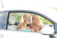 Happy female friends using digital tablet in car on sunny day