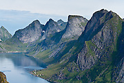 Above the Arctic Circle, ascend a slippery steep trail to Reinebringen for spectacular views of sharply glaciated peaks surrounding Reinefjord, on Moskenesøya (the Moskenes Island), Lofoten archipelago, Nordland county, Norway.