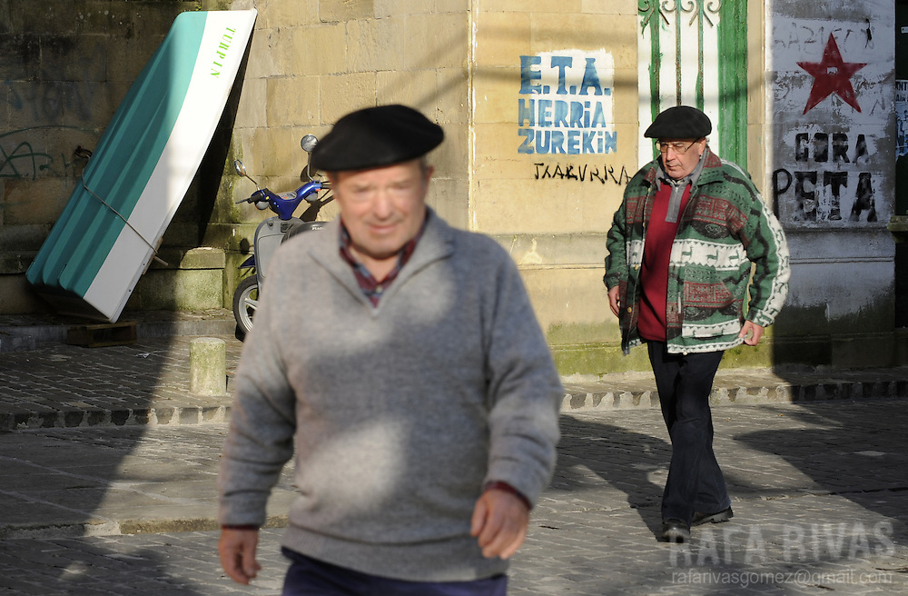 Two unidentified men walk past graffiti in favour of armed Basque group ETA, in the northern Spanish Basque village of Pasajaes de San Pedro, on February 18, 2009.