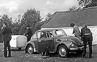 Police and forensic officers examine the Volkswagen car with a dog trailer attached in which three men, all Protestants, were gunned to death in a Provisional IRA gun attack. Sixty bullet holes were found in the car. The victims were: John Preshaw, 34 years, married, Hillsborough, Co Down; David Thompson, 34 years, Portadown; and Alfred Doyle, 24 years, married, Portadown. Alfred Doyle, Portadown, N Ireland, 24 years, married, part-time member, Uluster Defence Regiment, one of three Protestants, who were murdered just north of the N Ireland-Rep of Ireland border near Newry in a Provisional IRA gun attack. The three men were returning from the Munster Canine Show in Cork. 19750603458SOC2.<br /> <br /> Copyright Image from Victor Patterson, 54 Dorchester Park, Belfast, UK, BT9 6RJ<br /> <br /> t1: +44 28 9066 1296 (from Rep of Ireland 048 9066 1296)<br /> t2: +44 28 9002 2446 (from Rep of Ireland 048 9002 2446)<br /> m: +44 7802 353836<br /> <br /> victorpattersonbelfast@gmail.com<br /> victorpatterson@me.com<br /> <br /> www.victorpatterson.com<br /> <br /> Please see my Terms and Conditions of Use at https://www.victorpatterson.com/page2<br /> It is IMPORTANT that you familiarise yourself with them.<br /> <br /> Images used on the Internet incur an additional cost and must be visibly watermarked i.e. © Victor Patterson within the body of the image and copyright metadata must not be deleted. Images used on the Internet have a size restriction of 4kbs and are chargeable at rates available at victorpatterson.com.<br /> <br /> This image is available only for the use of the download recipient i.e. television station, newspaper, magazine, book publisher, etc, and must not be passed on to any third party. It is also downloaded on condition that each and every usage is notified within 7 days to victorpatterson@me.com<br /> <br /> The right of Victor Patterson (or the named photographer) to be identified as the author is asserted in accordance with The Copyright Designs And