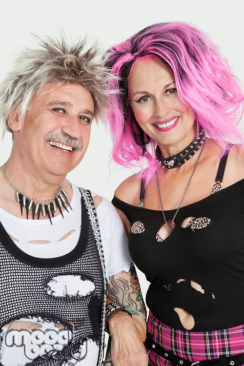 Portrait of senior punk couple standing with arm in arm over gray background
