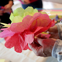 Connie Kelly makes a paper flower at Eco Chic Blossoms during the Day of the Dead Art Crawl in the Brooklyn Arts District. (Jason A. Frizzelle)