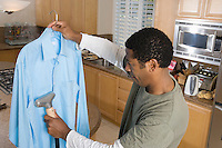 Mid-adult woman cleaning shirt in domestic kitchen