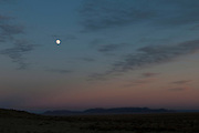 In this picture from New Mexico there is a full moon in the distant sky after the sun has set.