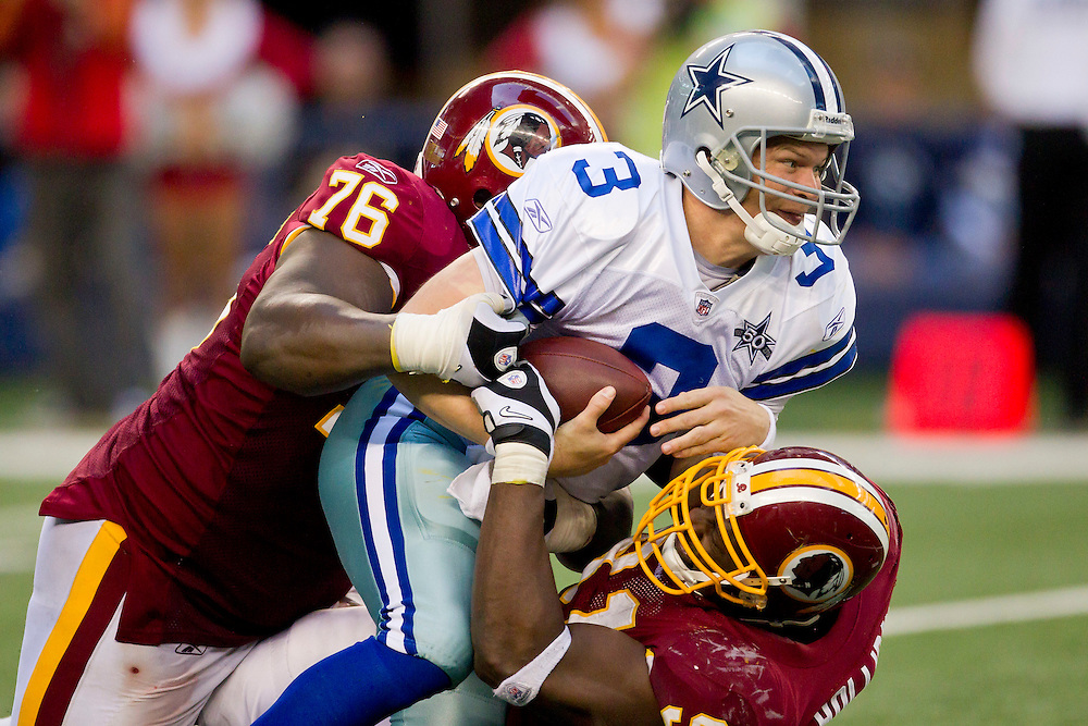 ARLINGTON, TX - DECEMBER 19:   Jon Kitna #3 of the Dallas Cowboys is tackled by Anthony Bryant #76 and Vonnie Holiday #91 of the Washington Redskins at Cowboys Stadium on December 19, 2010 in Arlington, Texas.  The Cowboys defeated the Redskins 33-30.  (Photo by Wesley Hitt/Getty Images) *** Local Caption *** Jon Kitna