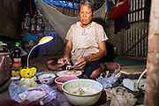 30 AUGUST 2013 - BANGKOK, THAILAND: A woman eats dinner by herself with only a desk lamp for light in her hut at a construction site in the Bang Na section of Bangkok near Suvarnabhumi International Airport. The workers are building a four storey apartment building. They will live on the site for approximately one year, until the building is close to opening. They are paid the Thai minimum wage of 300 Baht per day, approximately $10 US.       PHOTO BY JACK KURTZ