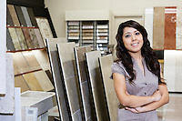 Portrait of a happy store clerk standing with arms crossed in tile shop