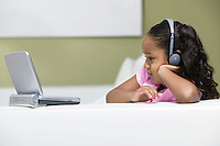 Little Girl on sofa Watching movie on Portable DVD Player side view