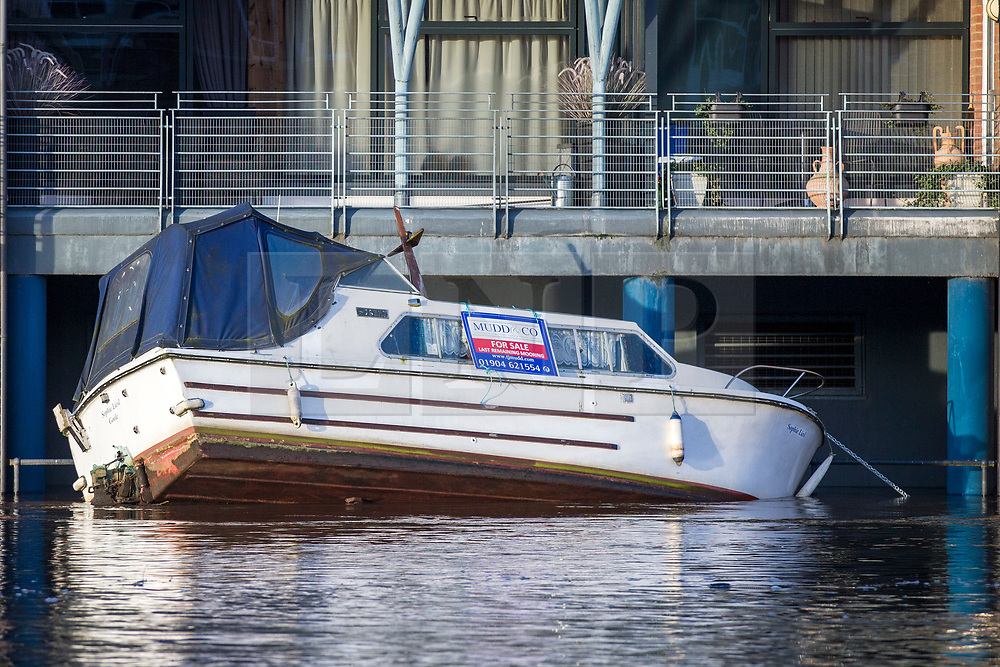 © Licensed to London News Pictures. 18/03/2019. York UK. A boat sits on its side this morning in a block of flats next to the river Ouse in York city centre after recent heavy rain caused overnight flooding. Photo credit: Andrew McCaren/LNP