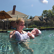 A mother with her four month old baby girl acclimating her daughter to the water in a back yard family swimming pool. Connecticut, USA. Photo Tim Clayton