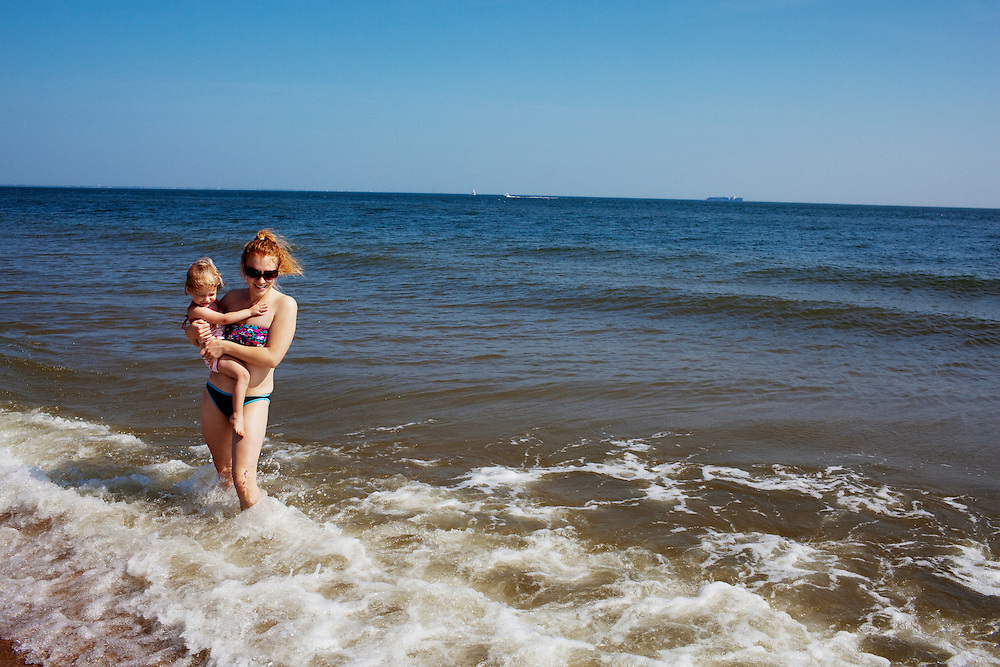 Melissa Eich, 22, and her daughter Madelyn, 2, enjoy the waves at the beach near Oceanview in Norfolk, Virginia on Saturday, May 15, 2010.