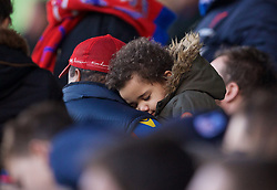 LONDON, ENGLAND - Saturday, February 21, 2015: A young Crystal Palace supporter is carried out asleep during the Premier League match against Arsenal at Selhurst Park. (Pic by David Rawcliffe/Propaganda)