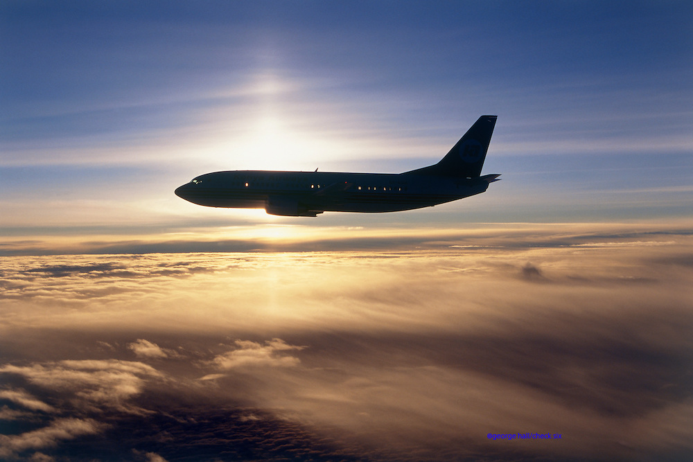 Airliner flying over sun lit clouds