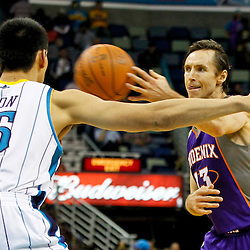 February 2, 2012; New Orleans, LA, USA; Phoenix Suns point guard Steve Nash (13) passes as New Orleans Hornets power forward Gustavo Ayon (15) defends during a game at the New Orleans Arena. The Suns defeated the Hornets 120-103.  Mandatory Credit: Derick E. Hingle-US PRESSWIRE