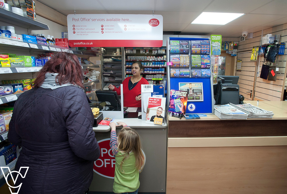 Pictured postmaster Kanchan Lakhman serving customer Marie Weston and daughter Caitlyn (four)<br /> <br /> Thringstone Post Office, 19-23 Loughborough Road, Thringstone, Leicestershire.<br /> Date: January 23, 2015