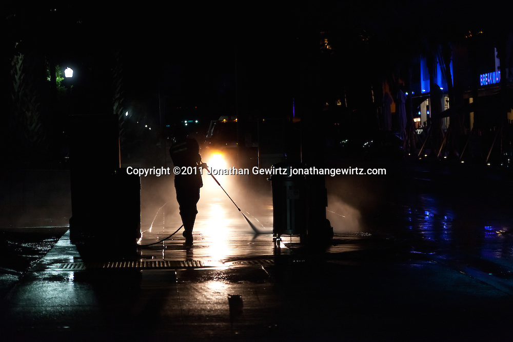 A Miami Beach municipal employee pressure washes the sidewalk during early morning hours. WATERMARKS WILL NOT APPEAR ON PRINTS OR LICENSED IMAGES.