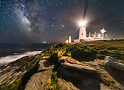 The Milky Way rises over the ocean above crashing surf and the iconic rocky shoreline of the coast of Maine. Pemaquid Point Lighthouse and it's beacon shine in the night sky, casting light on the ground in front of me and capturing the flag waving in the breeze.