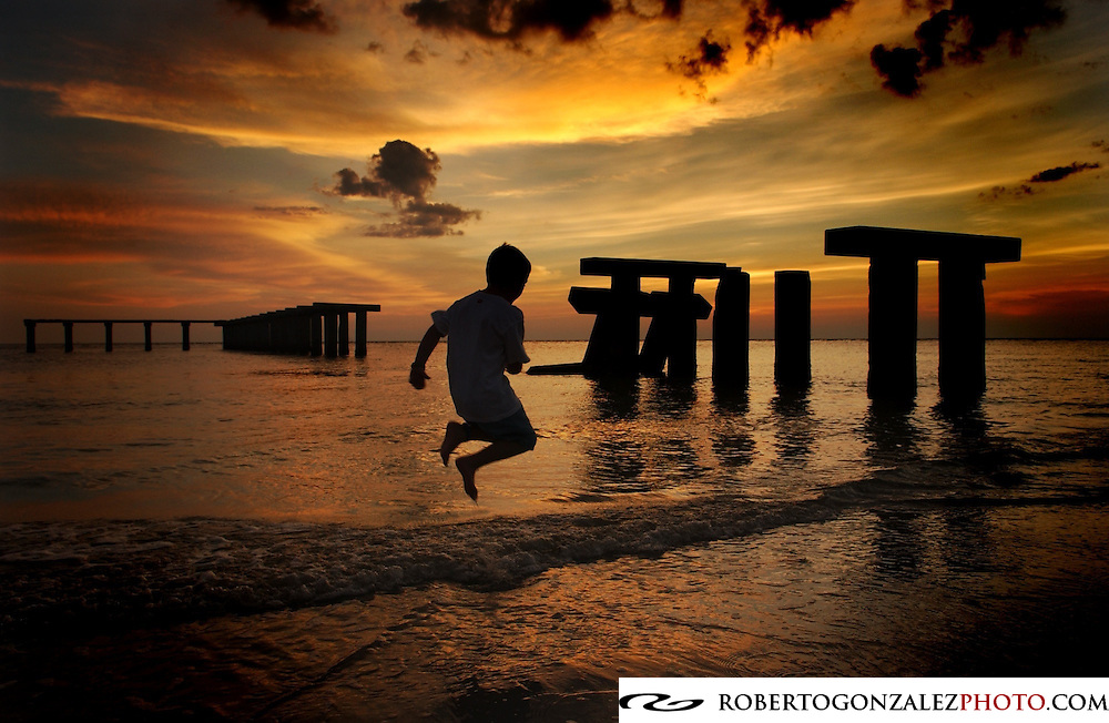 a child jumps along the beach on Boca Grande on Florida's gulf coast.
