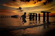 a child jumps along the beach on Boca Grande on Florida's gulf coast.