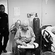 Nola Fontenot, center, plays the omnichord and sings church songs for Jimmie Burnett as he sleeps. Fontenot, a retired prison chaplain, visits patients in the prison hospital ward once a week. Corrections officer Cadet King looks on.