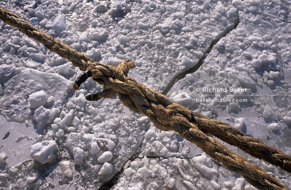 The detail of diagonal rope that holds a ship in winter ice, on the Saint Lawrence River, on 11th January 1999, in Quebec City, Quebec, Canada.