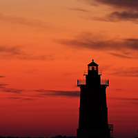 The historical Delaware Breakwater Light (est. 1885) silhouetted against a colorful sky near the end of civil twilight on a mid-November evening.  Photographed from Cape Henlopen State Park, Lewes, Delaware.