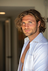 sexy man with long brown hair and blue eyes in a white open shirt