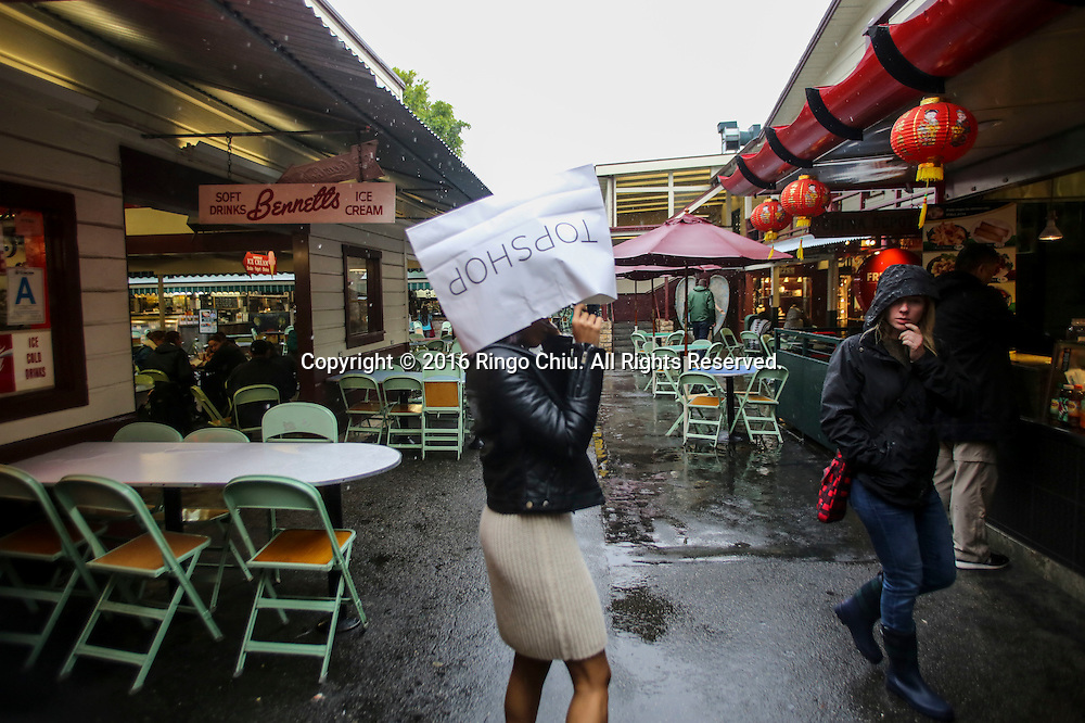 A woman covered her head by a shopping bag under the rain at Farmer Market in Los Angeles.(Photo by Ringo Chiu/PHOTOFORMULA.com)<br /> <br /> Usage Notes: This content is intended for editorial use only. For other uses, additional clearances may be required.