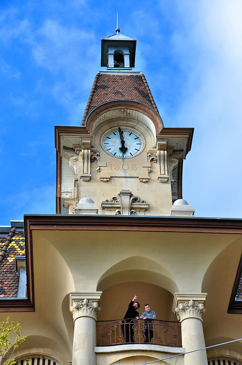 Two Men in Balcony Below Clock Tower in Ouchy, Switzerland<br /> The one man is probably pointing at the wonderful scenery of the Ouchy harbor, Lake Geneva, and the Swiss Alps from the balcony of his room beneath the clock and bell tower of the Aulac Hotel.  This three star hotel, which was built in 1906, has an ideal setting in Ouchy, which is a seaside village a short distance from Lausanne, Switzerland.