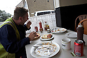 A greasy spoon cafe fry-up breakfast for a worker surrounded by dirty crockery left by his mates in industrial Grays, Essex